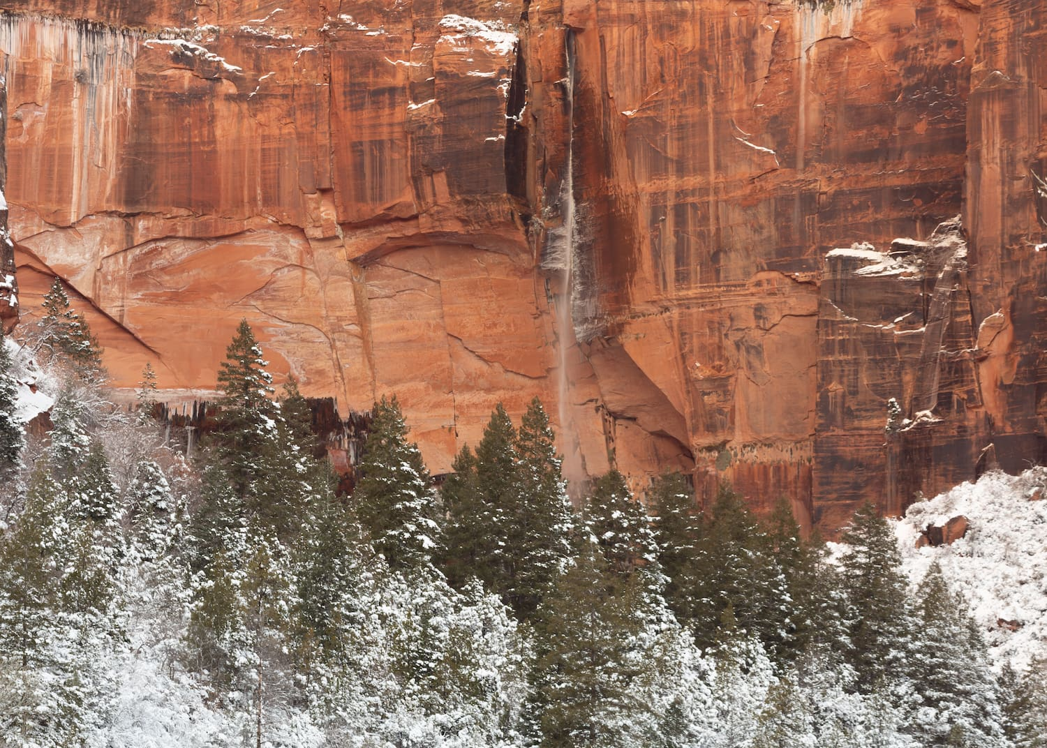 A narrow waterfall streams down a red sandstone cliff face in front of snow covered hills and pine trees.