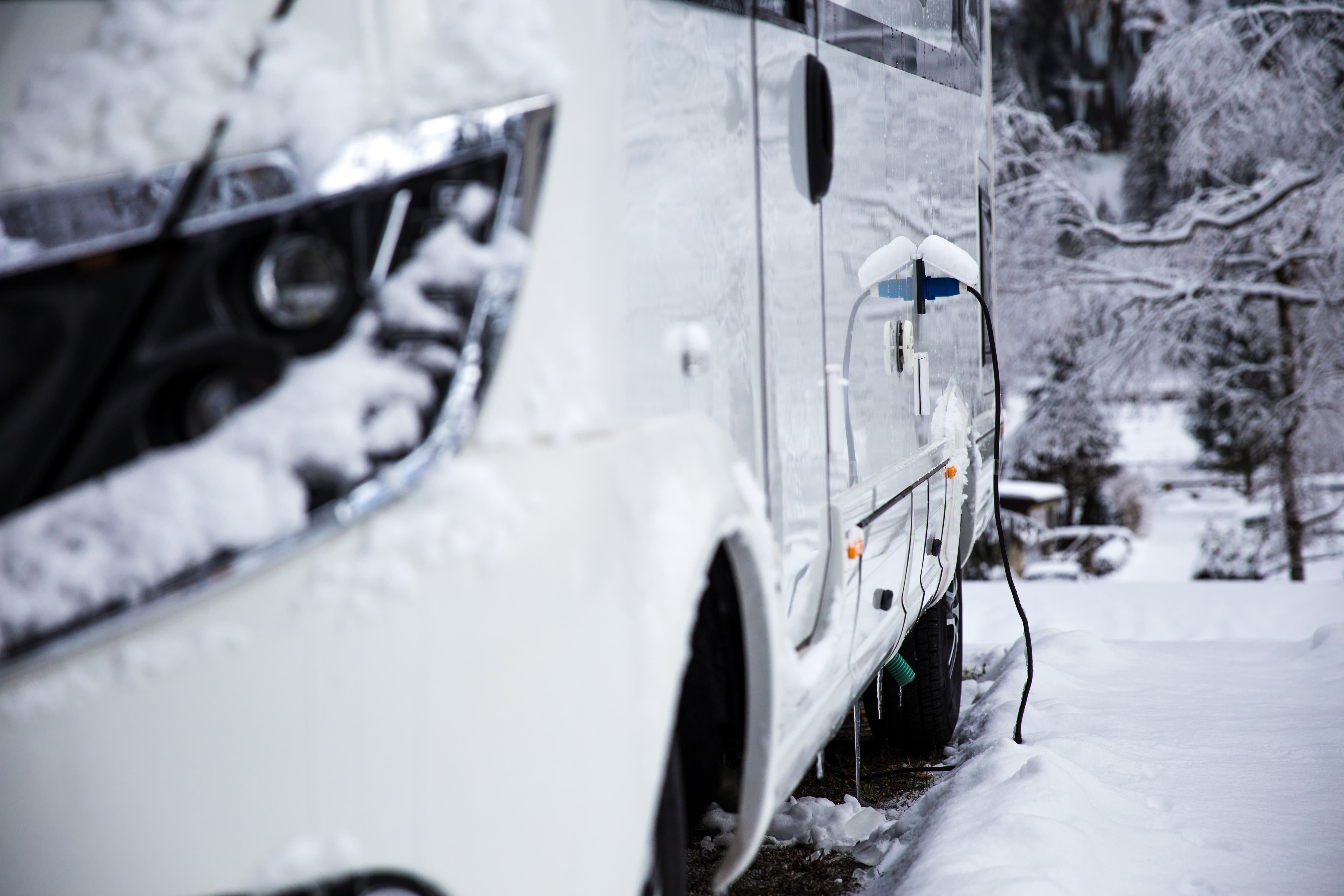 rv camped in the snow with electric input plugged in
