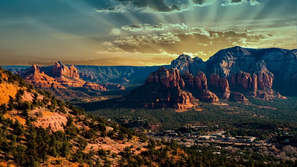 Sun rays emulating from behind rock formations in the red rock landscape of Sedona Arizona at sunset.