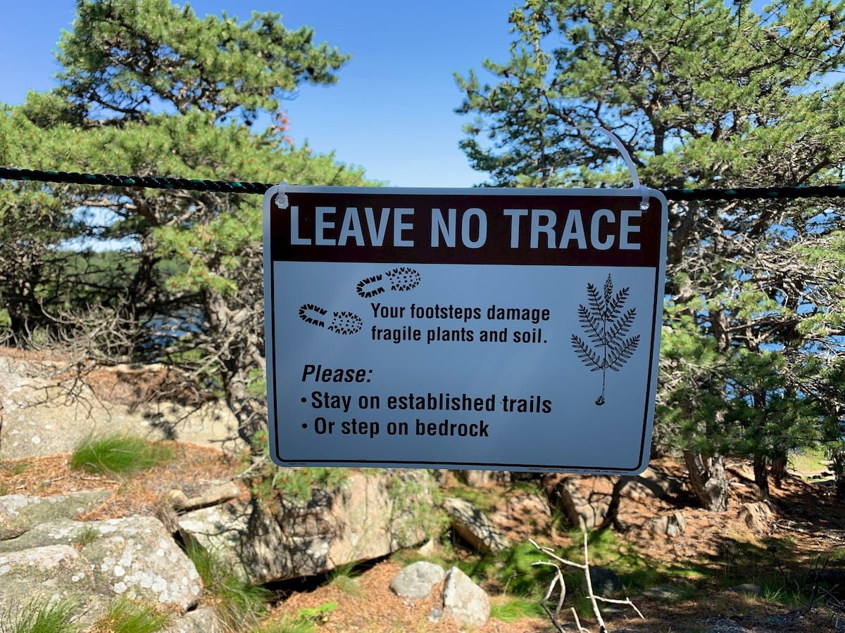 Natural landscape with a leave no trace sign in front of it.
