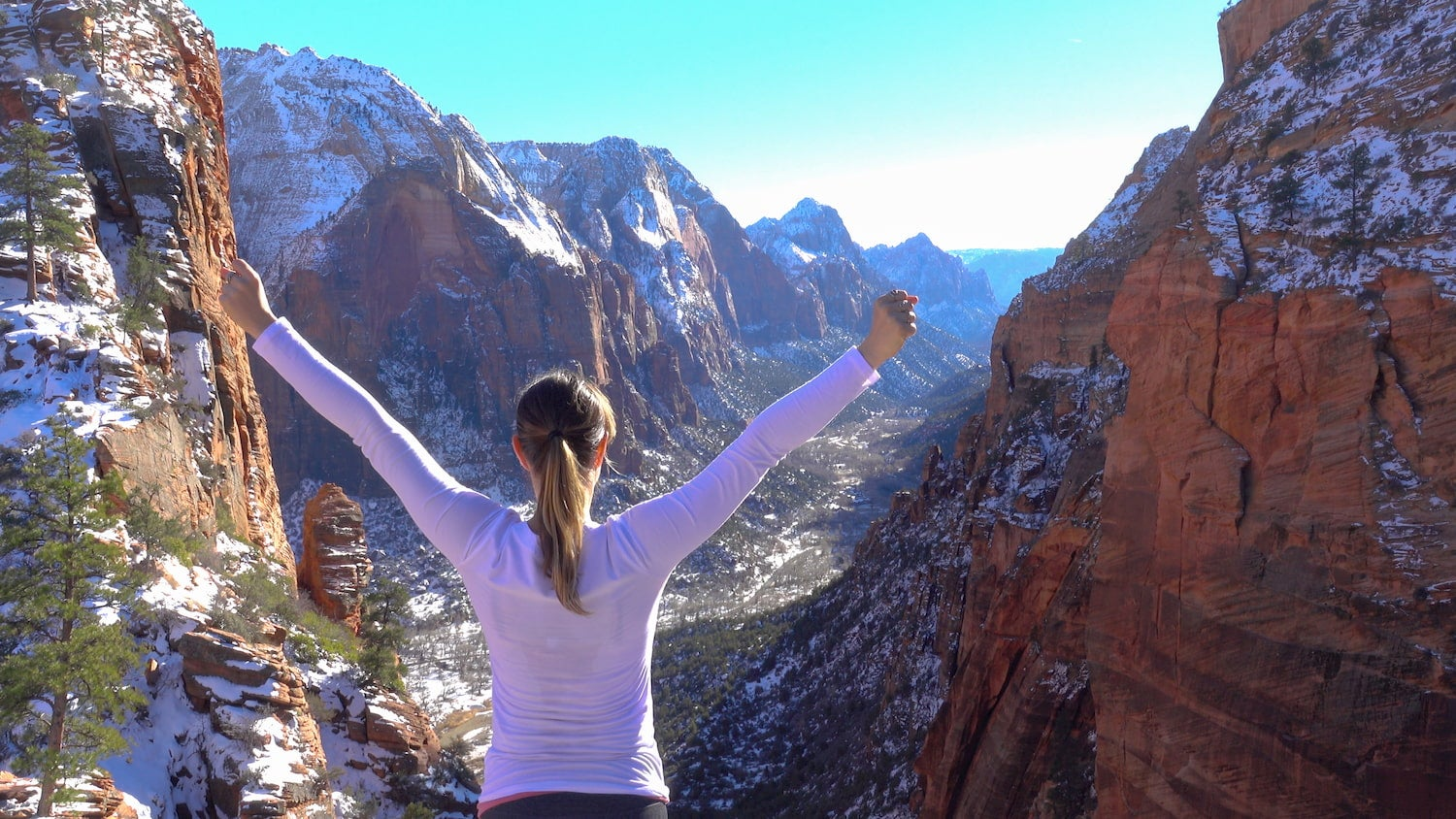 woman with arms raised in celebration in Zion National Park in winter