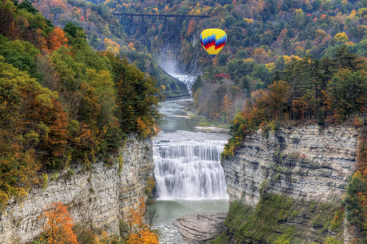 hot air balloon over waterfall at middle falls at letchworth state park