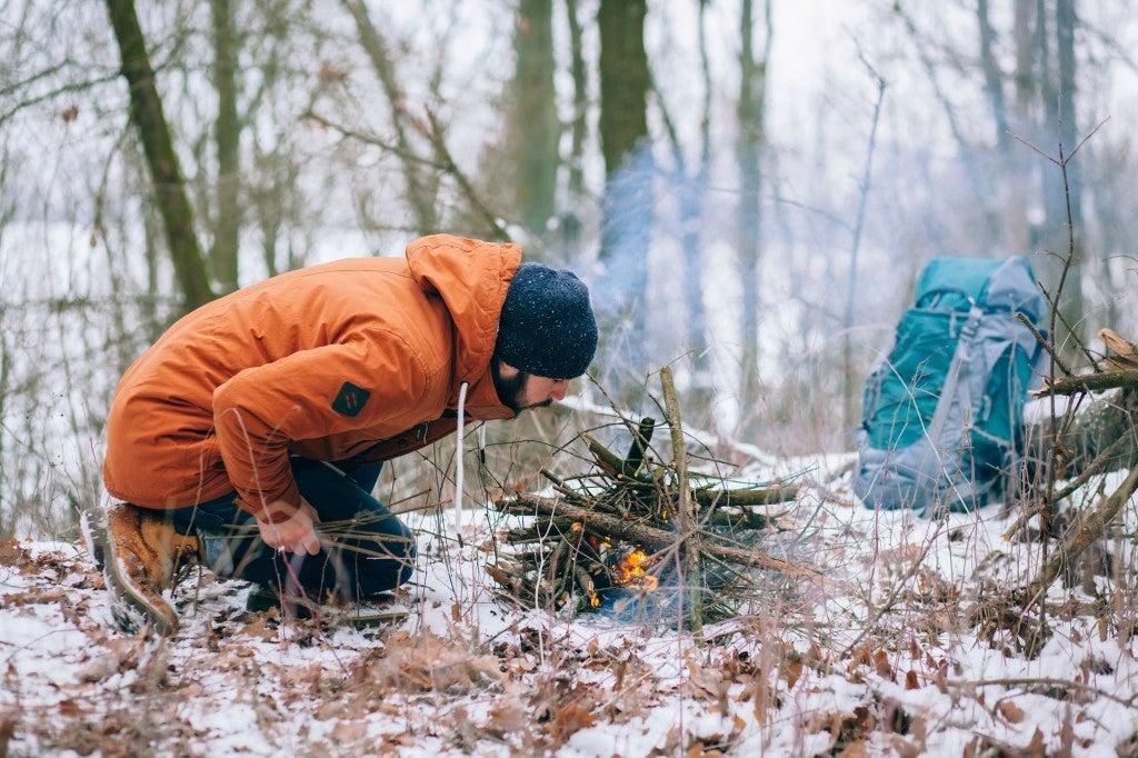 man in snowy woods building fire