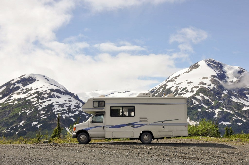 parked rv with snowcapped mountains just beyond it