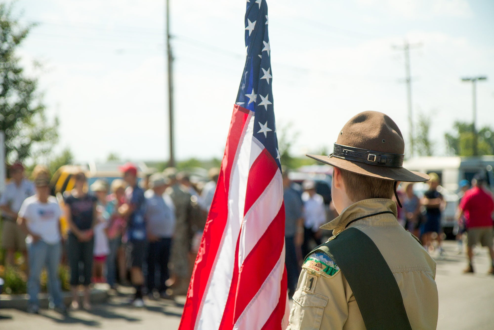 Eagle Scout holding an American flag at an event.