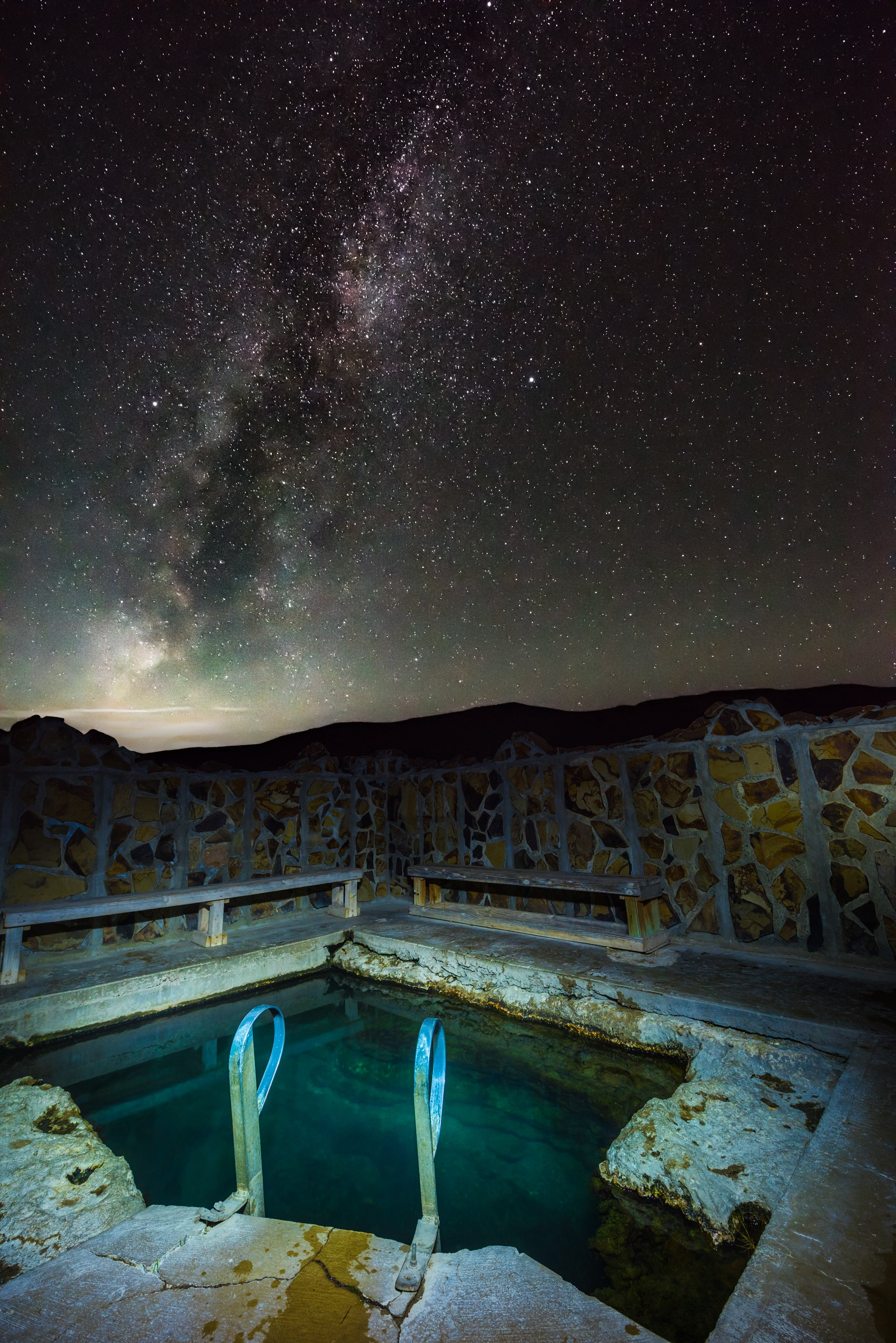 Hot springs at night under the star filled sky with a ladder and brick pool.