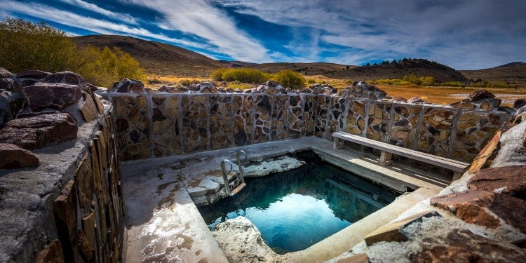 Hot spring surrounded by brick wall and pool with stairs in the mountains.