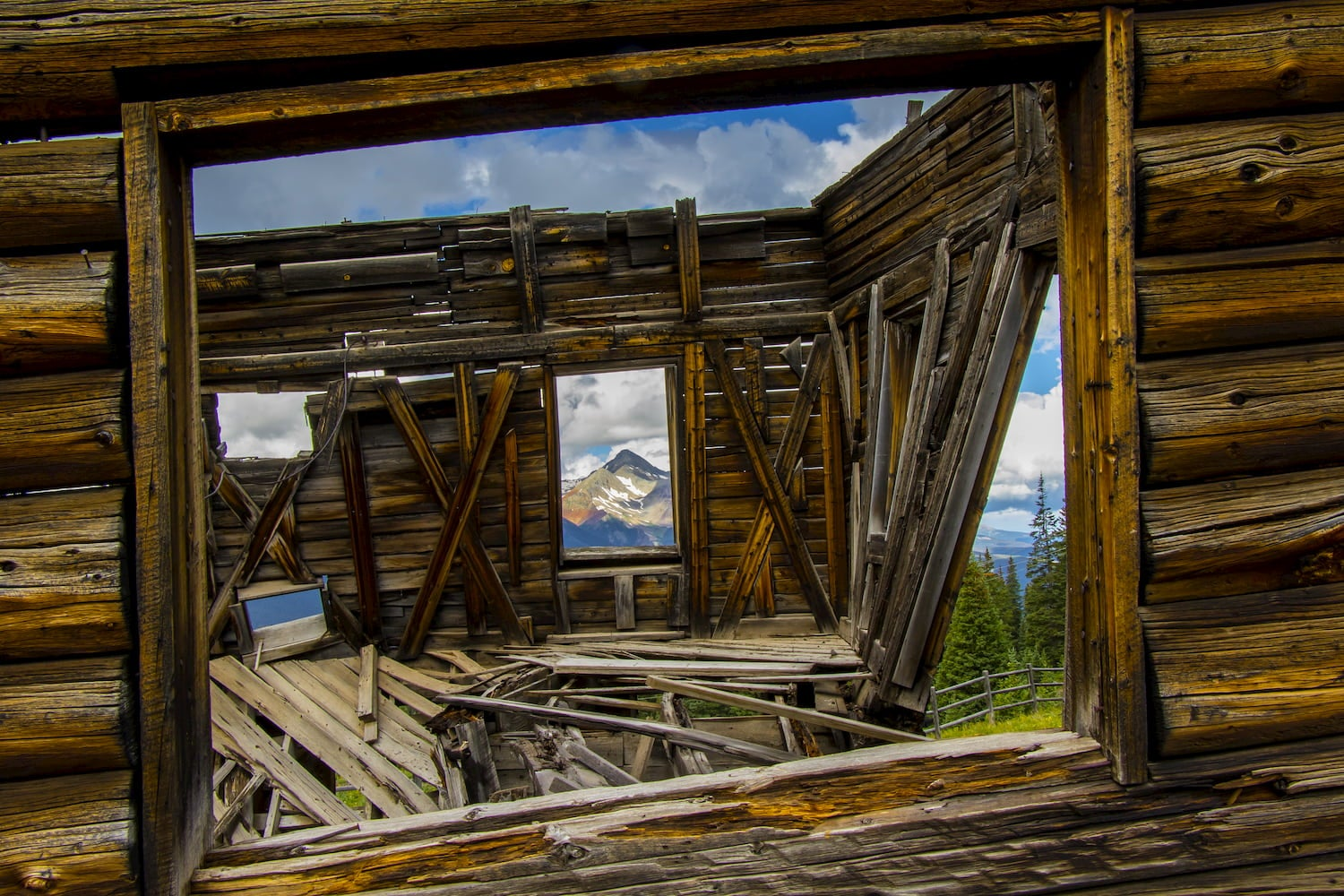 Telluride in Colorado's San Juan Mountains, summer - abandoned mining structure at ghost town of Alta with Wilson Peak viewed through window.