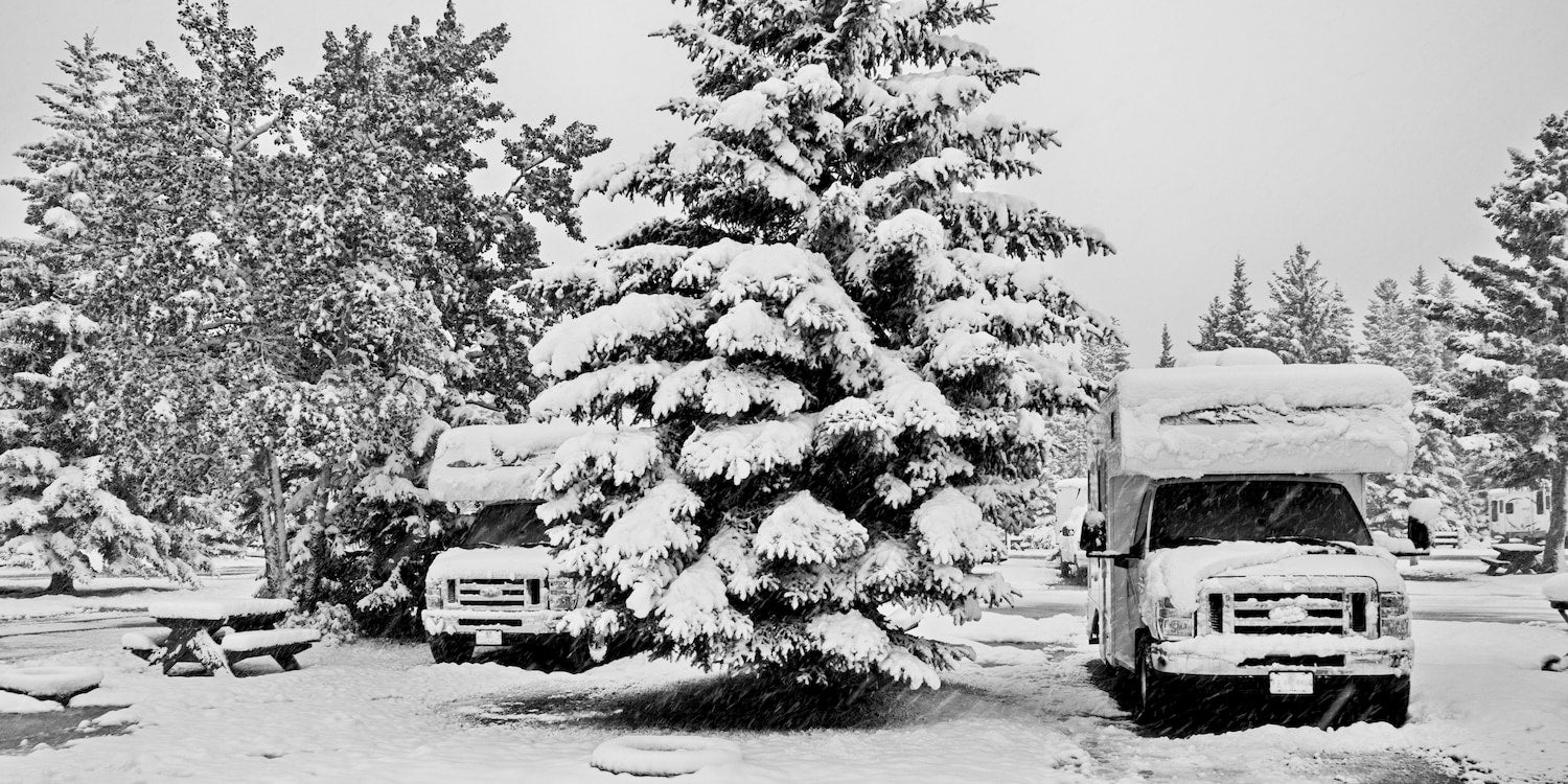 two rvs parked at adjacent snow covered campgrounds