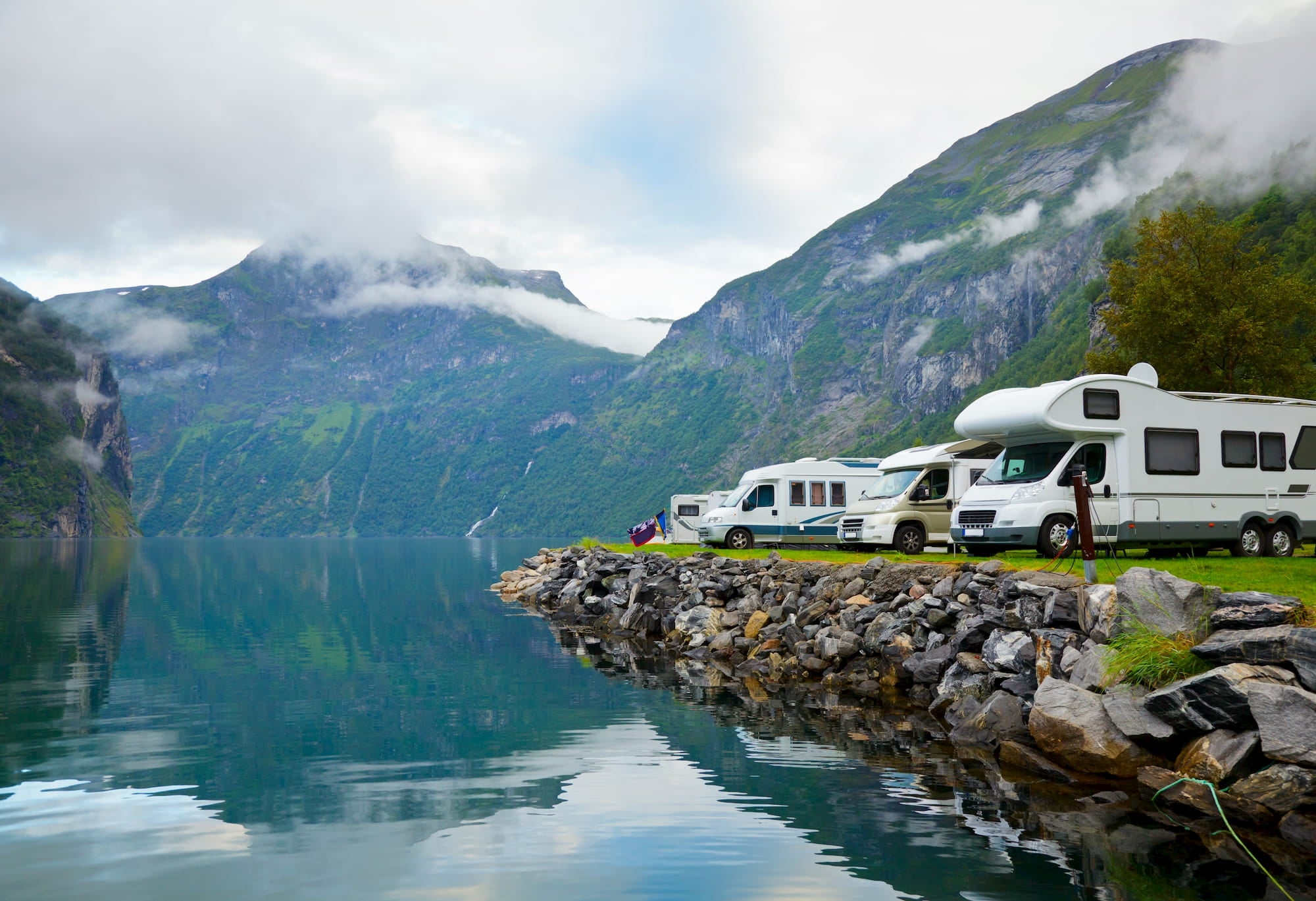 line of rvs next to water and in front of mountains