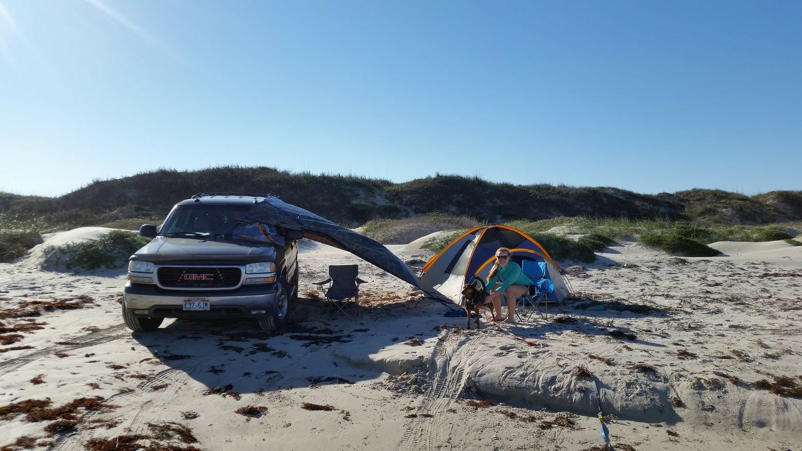 Women set up beside tent and SUV on the beach.