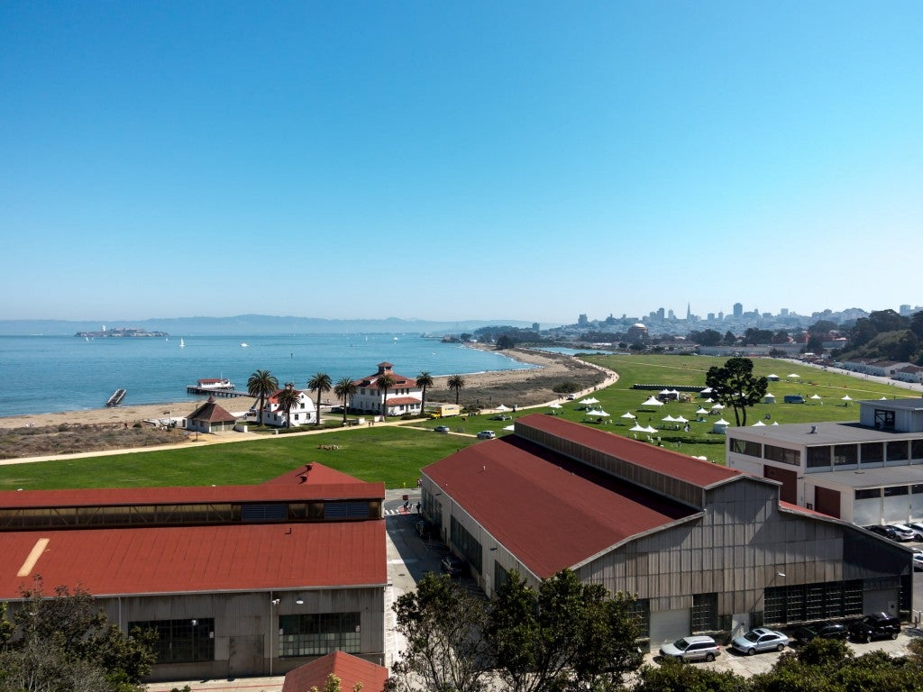 Presidio in San Fransisco, large buildings in foreground and large grass field and ocean in background