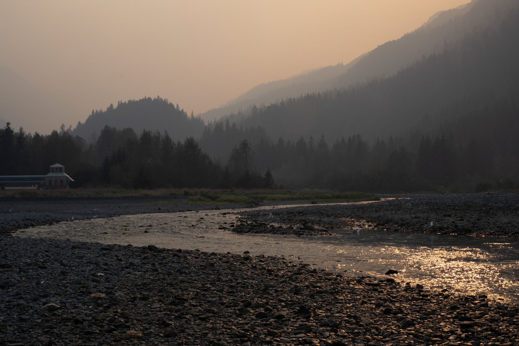 Hazy sunset over mountainous landscape with river flowing through it.