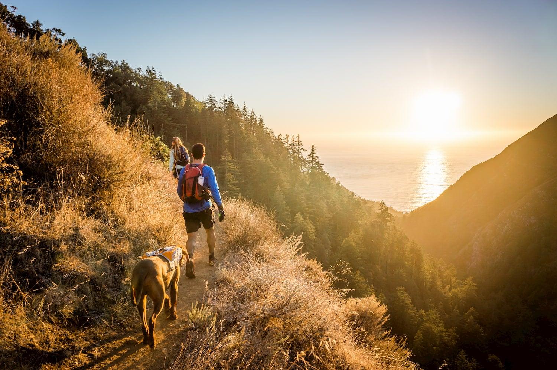 man woman and dog hiking at Big Sur