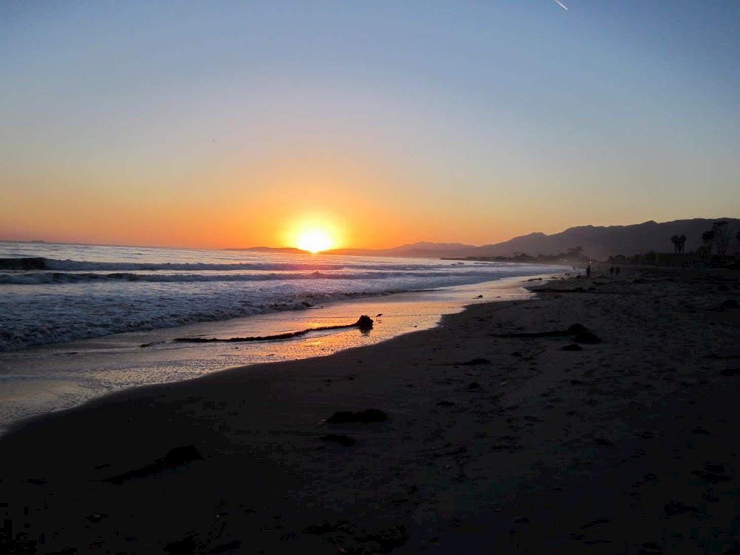 Sunset over a beach with oceanside cliffs.