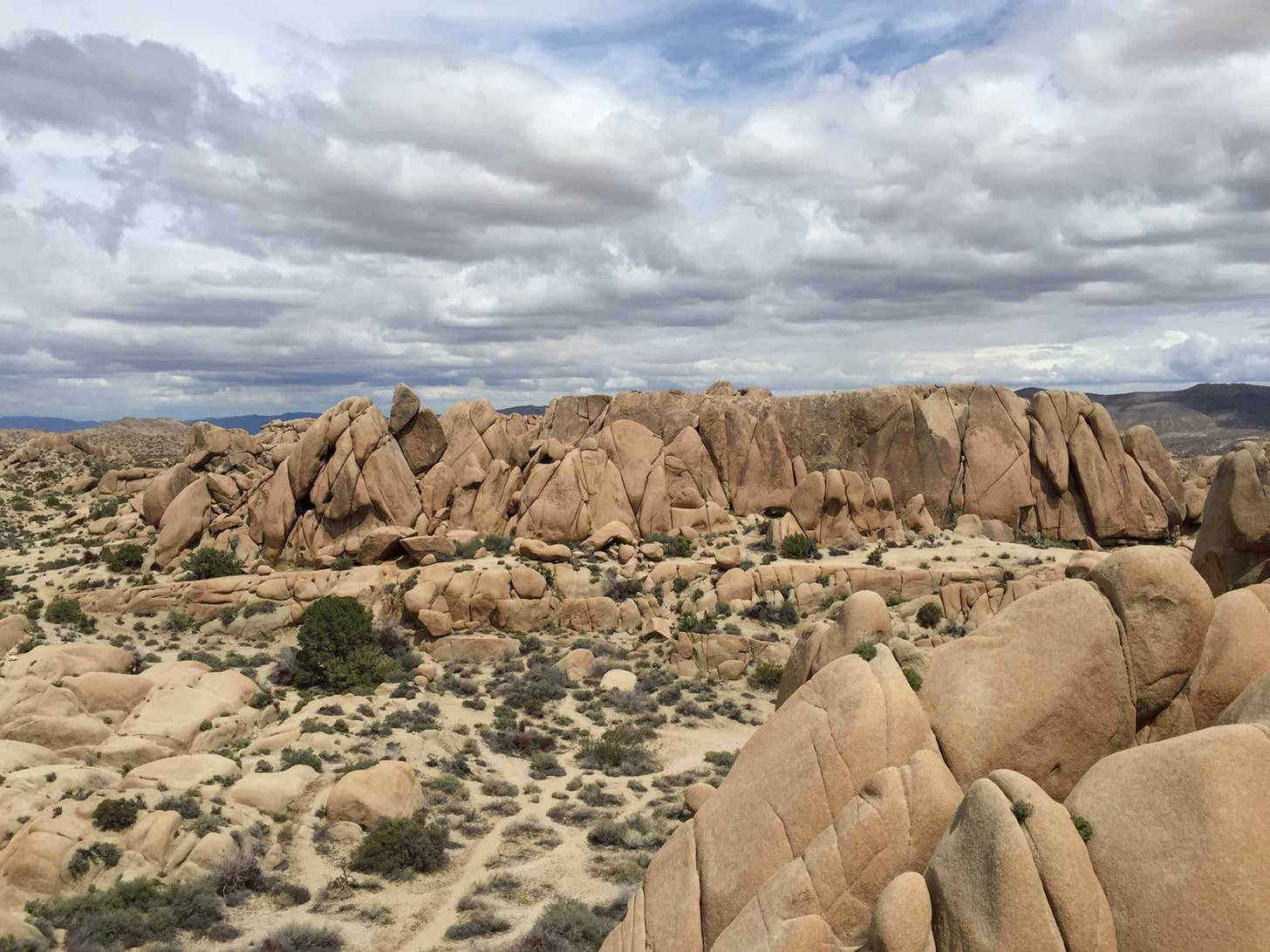 Cloud sky over a landscape of large boulders in the desert.
