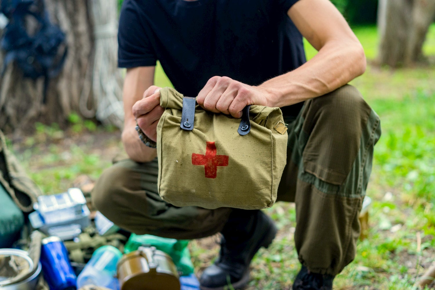 man holding large first aid kit out in the wilderness