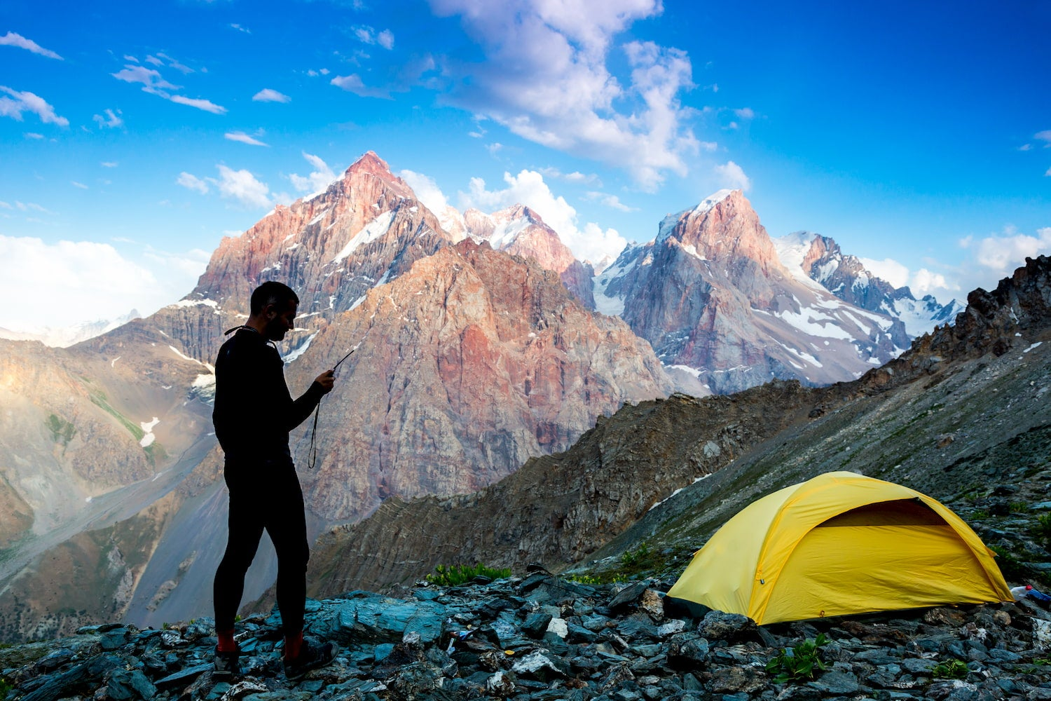 man on mountain top looking at phone with tent nearby