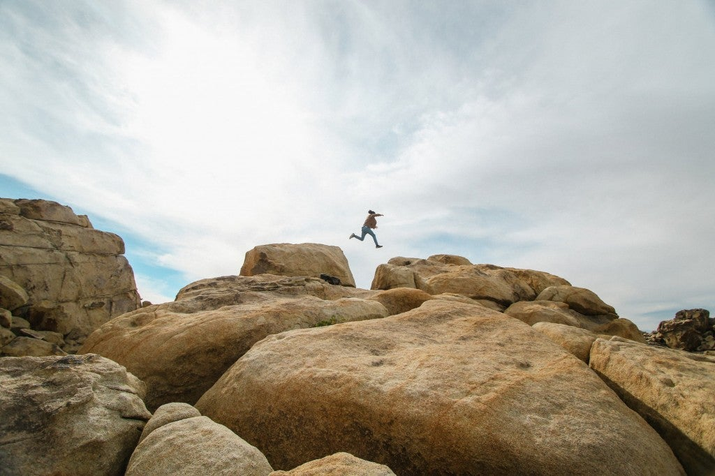 Person running and jumping over large boulders.