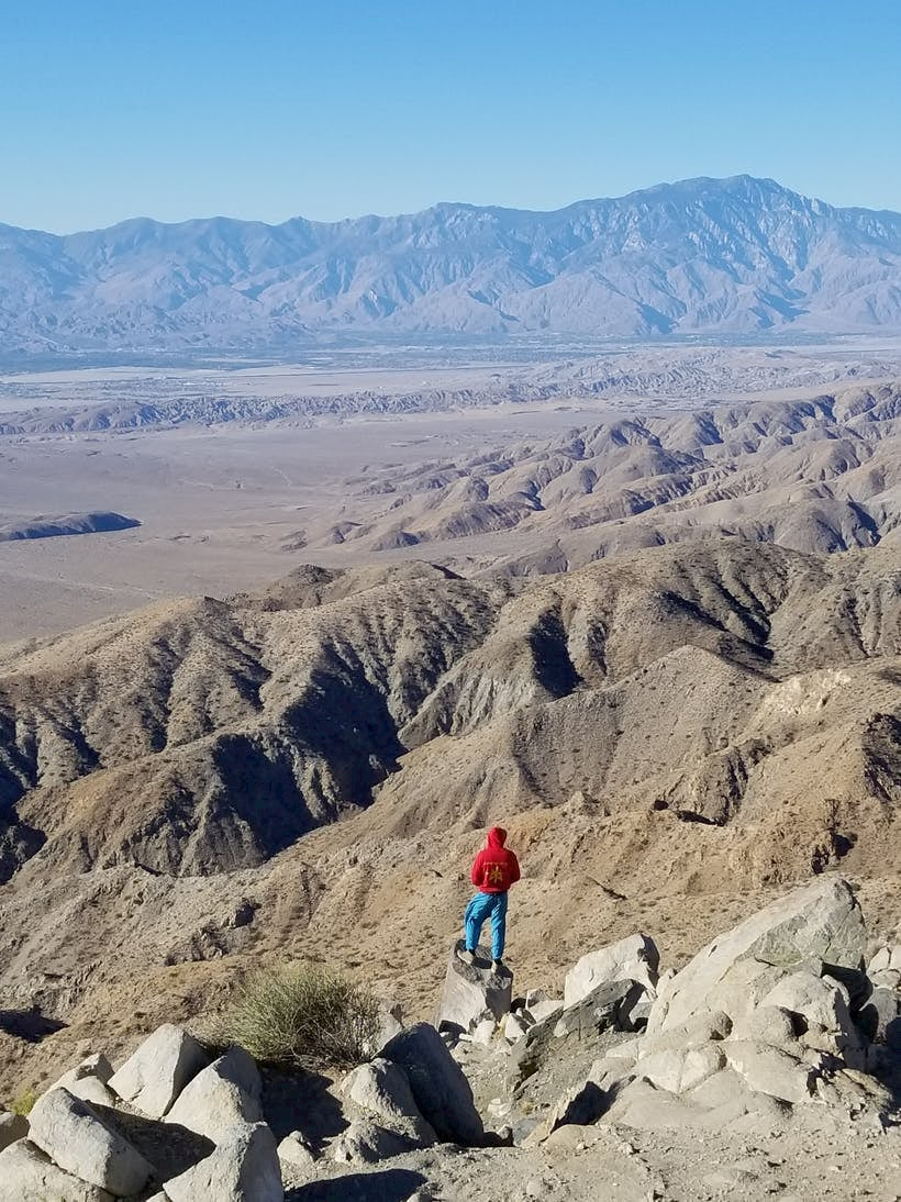 Person standing on large boulder overlooking desert mountains.