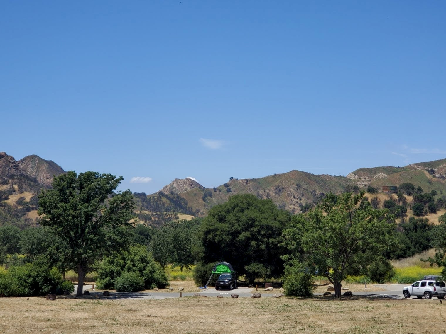 cars parked inna field with a pop up tent on one of them with trees and mountains in the background.