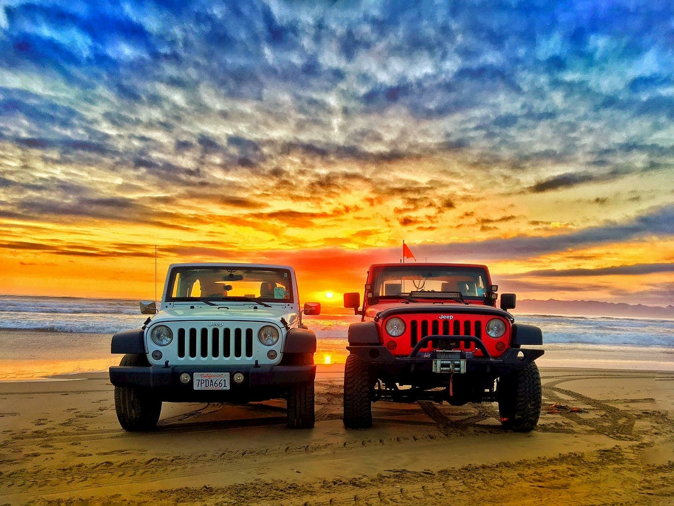 Two jeep wrangles parked beside each other on the beach at sunset.