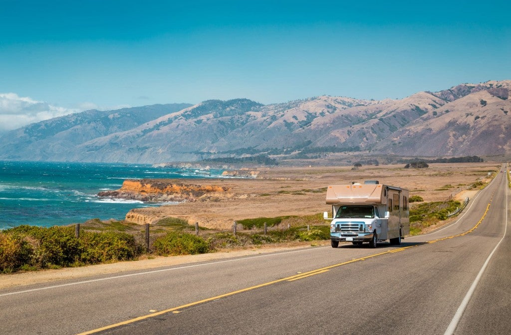 RV driving along the California coast beside the pacific ocean with mountains in the background.