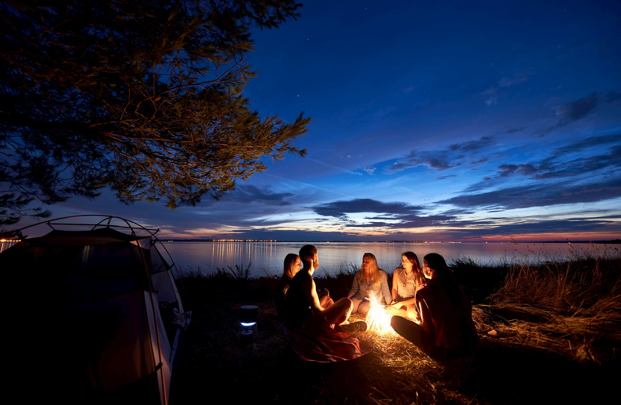 Night summer camping on sea shore. Group of five young tourists sitting on the beach around campfire near tent under beautiful blue evening sky.