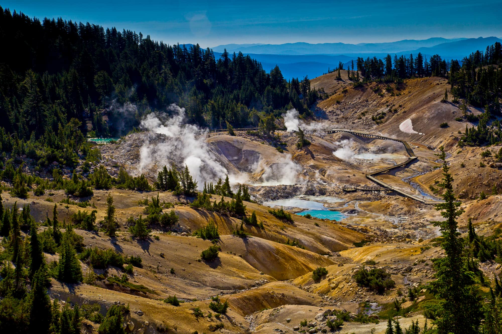 Textured geothermal valley with yellow tinted ground, bright blue ponds, winding path, and mountains in the background.
