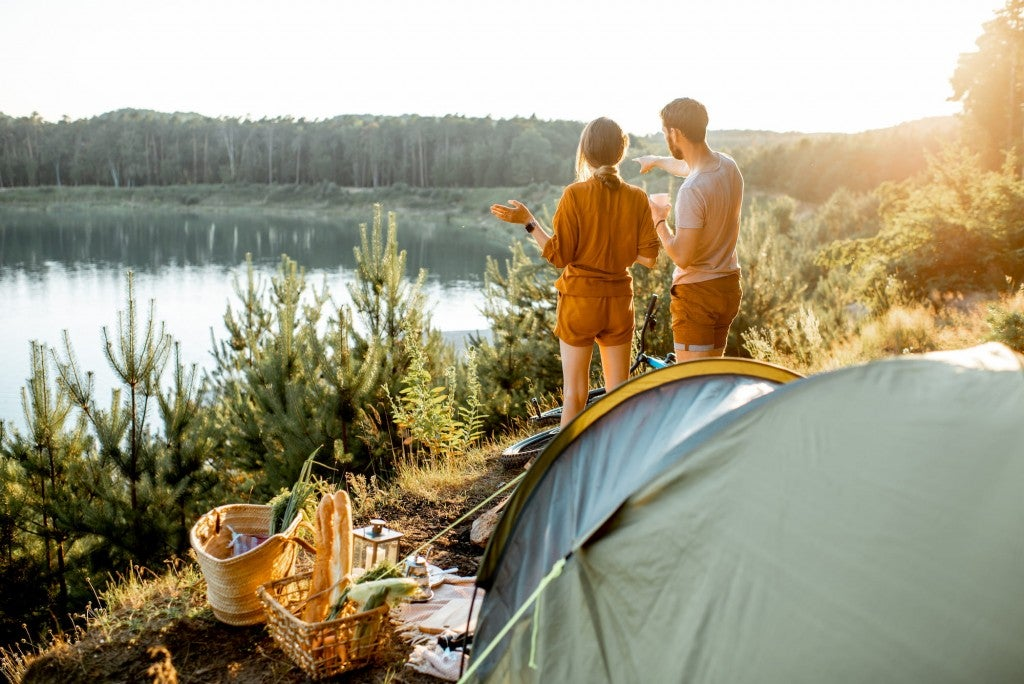Young couple looking out over a lake beyond their campsite with a tent and blanket.