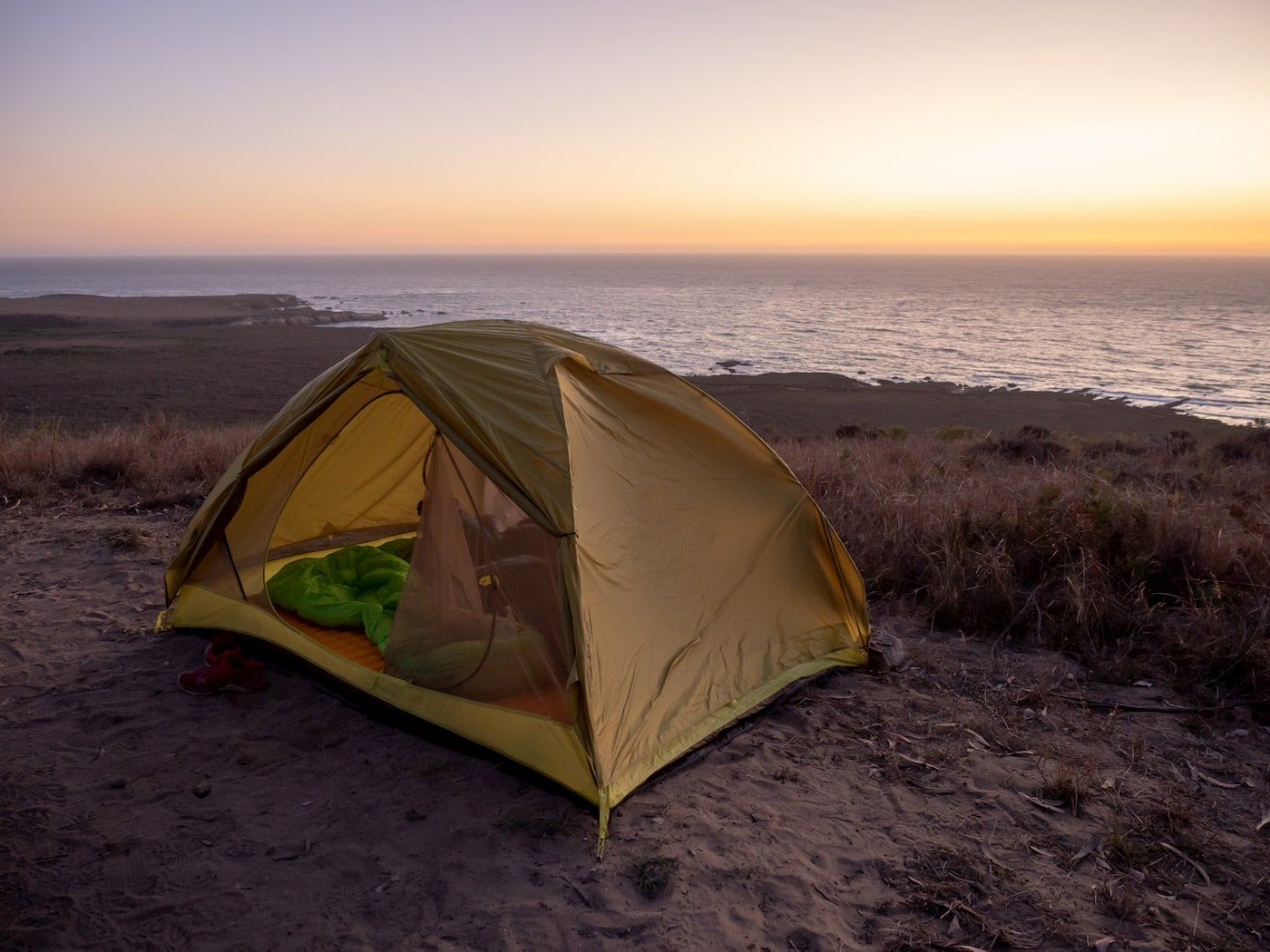 Tent set up in the dunes beside the pacific ocean at sunset.