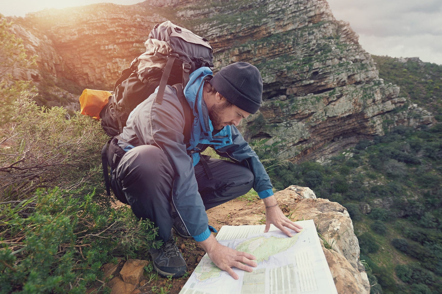 backpacking man looking at a map spread out over a rock