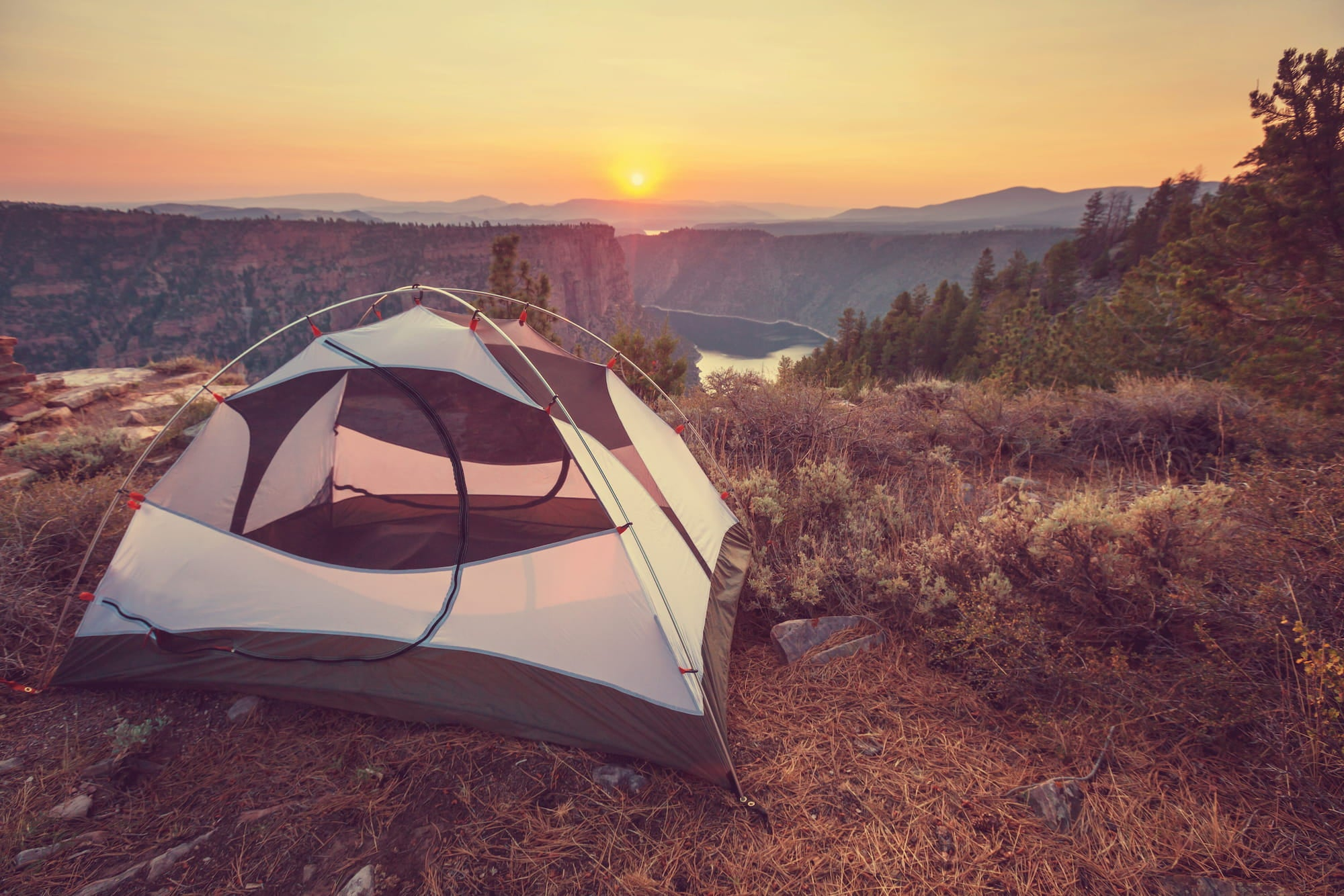 Tent setup on the side of a gorge at dusk.