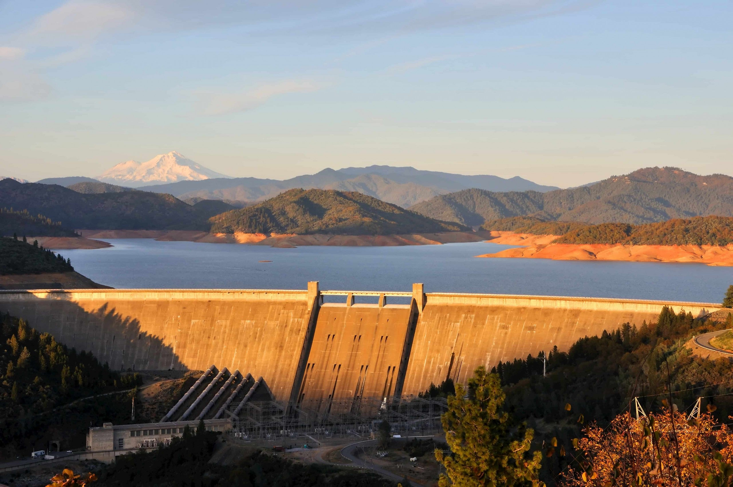 Golden sunlight over the Shasta Dam with MT. Shasta and green hills in the background.