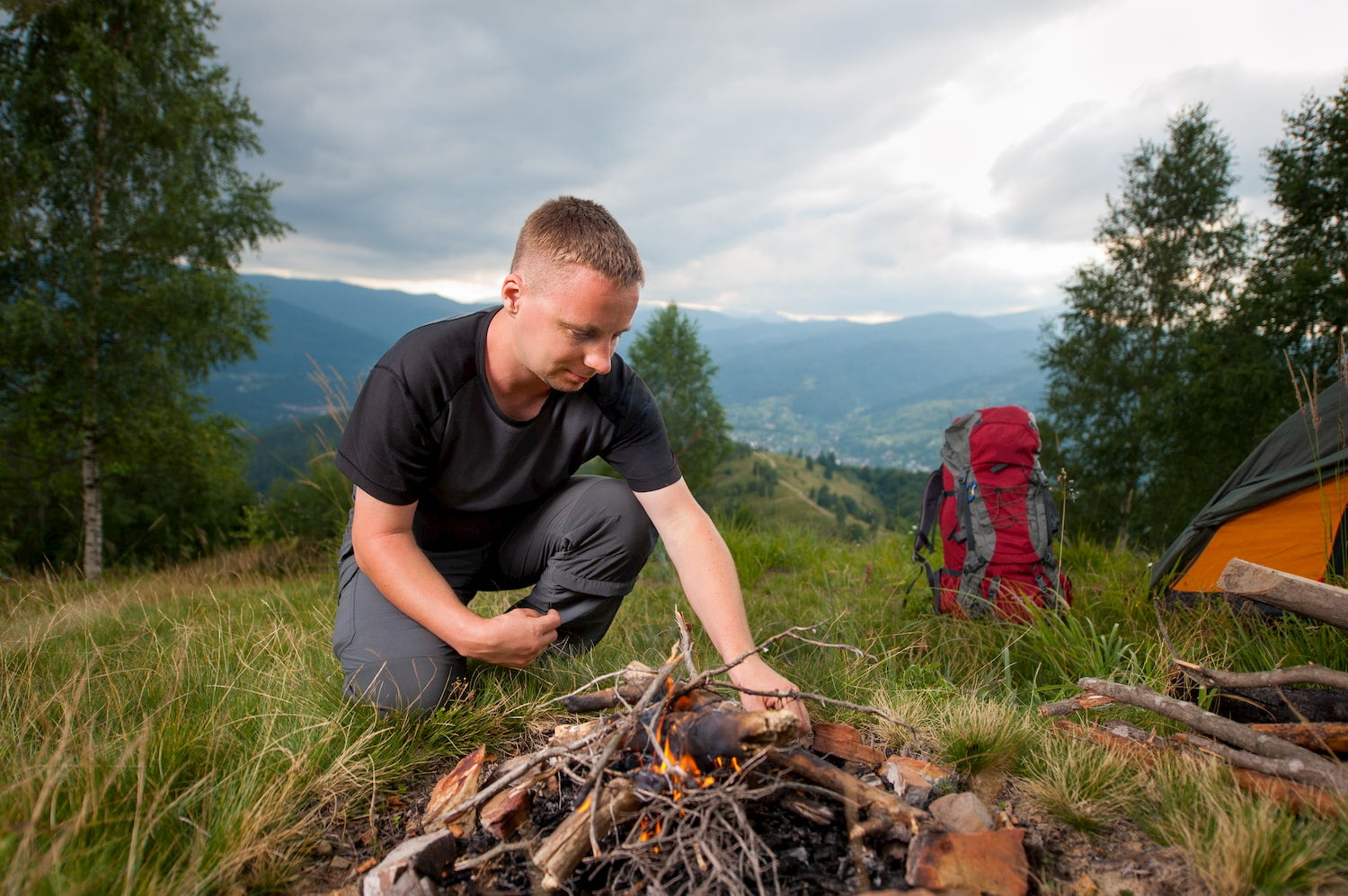 young man tourist kindling campfire on the hill with tent and travel backpack in background