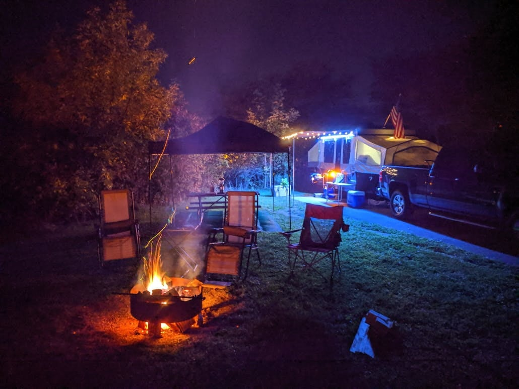 campfire at night with empty chairs and camping trailer in background