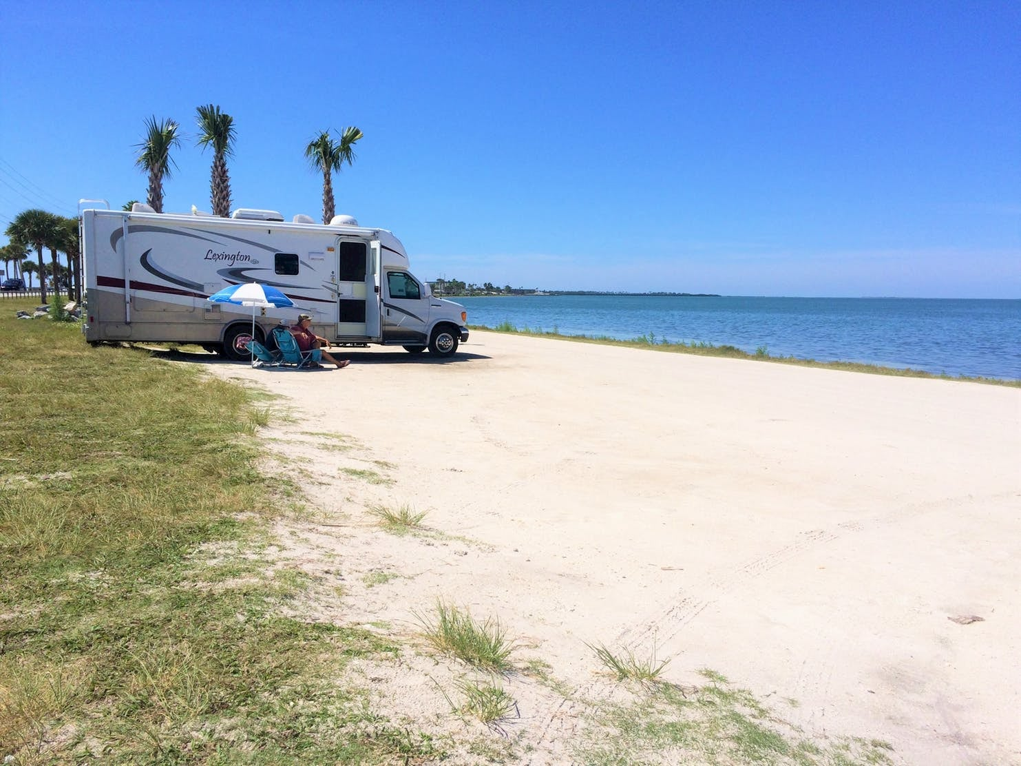 RV parked on the beach beside the ocean and palm trees.