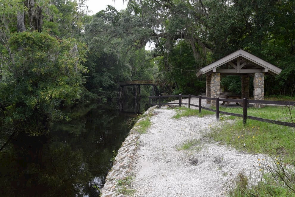Wooden shelter beside a river with a bridge over it.