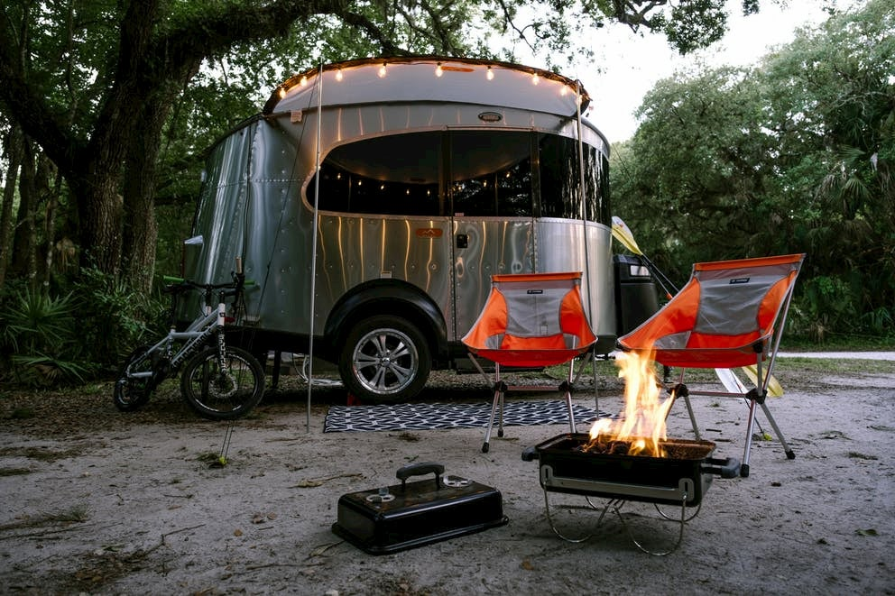 Tow trailer with string lights, camp chairs, and a lit barbecue in the forest.