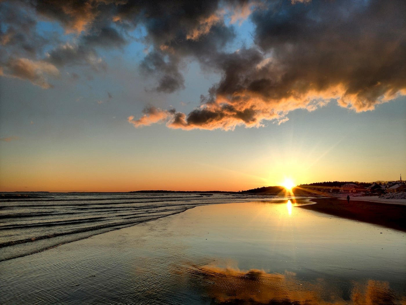 Sunset over a long stretch of beach at low tide.