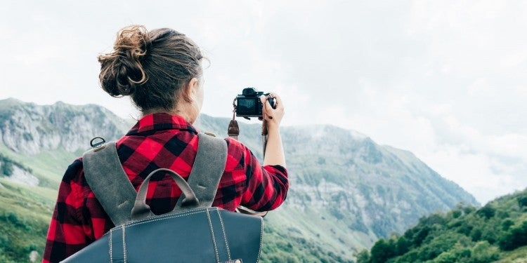 back of woman doing landscape photgraphy