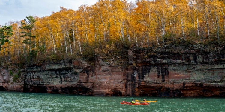 Two kayakers paddling beside a large forested cliff.