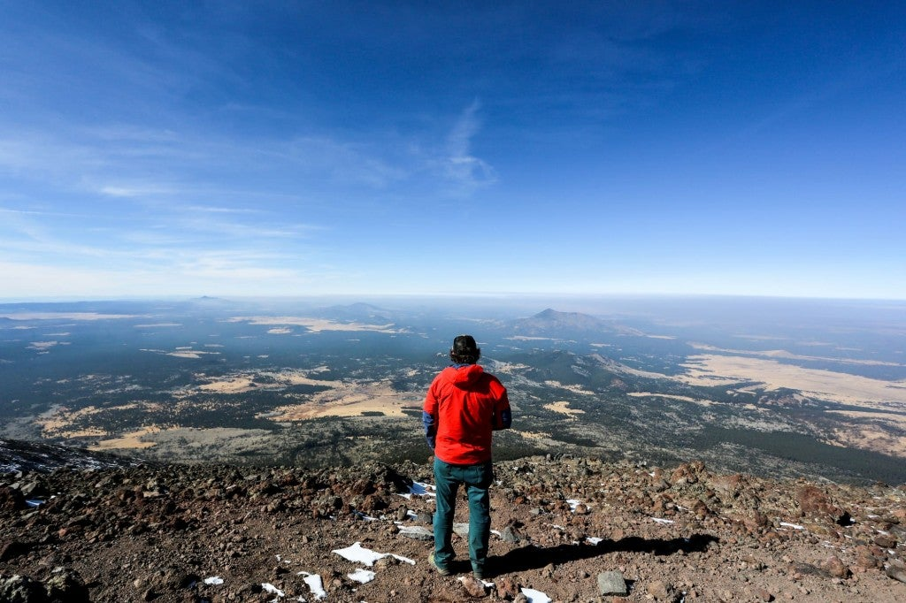 man standing on mountain overlooking landscape