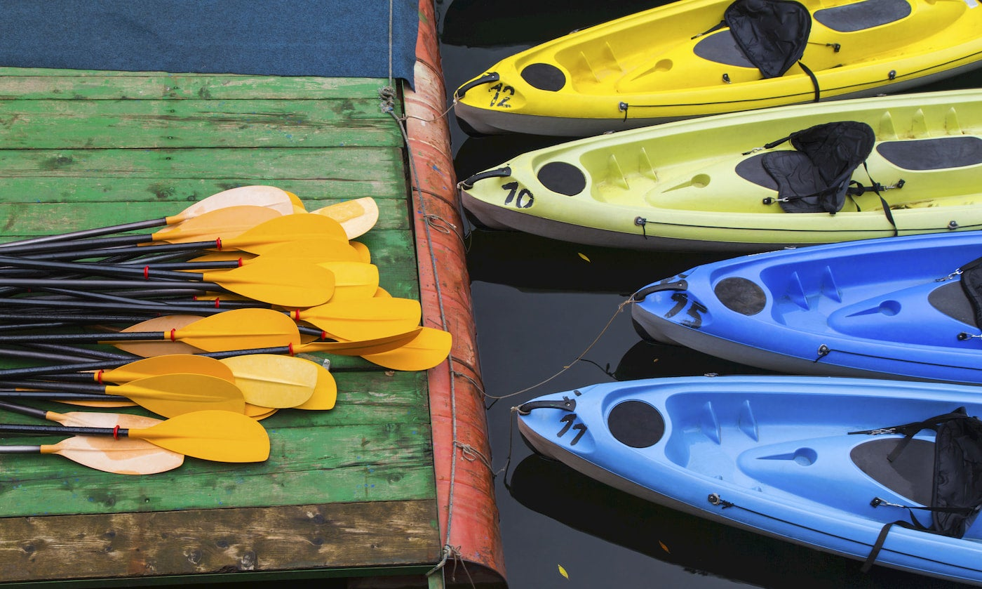 Kayaks tied up against a dock with a pile of paddles on it.