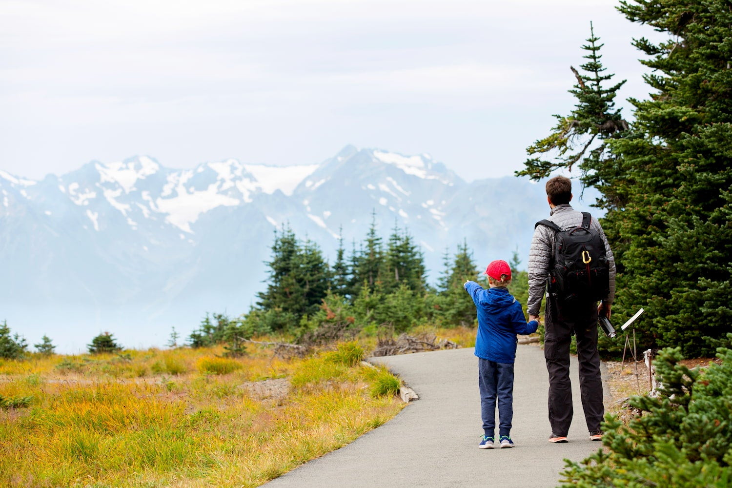 father and son on trail with child pointing at mountains