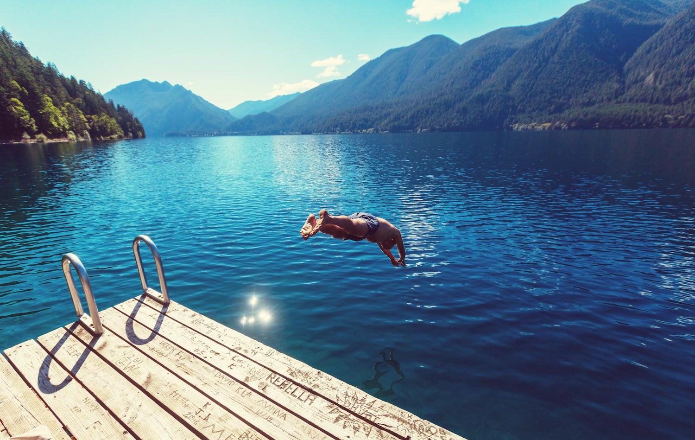 man jumping into lake crescent