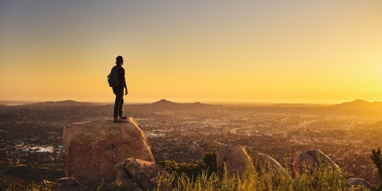 man on rock with landscape at sunset