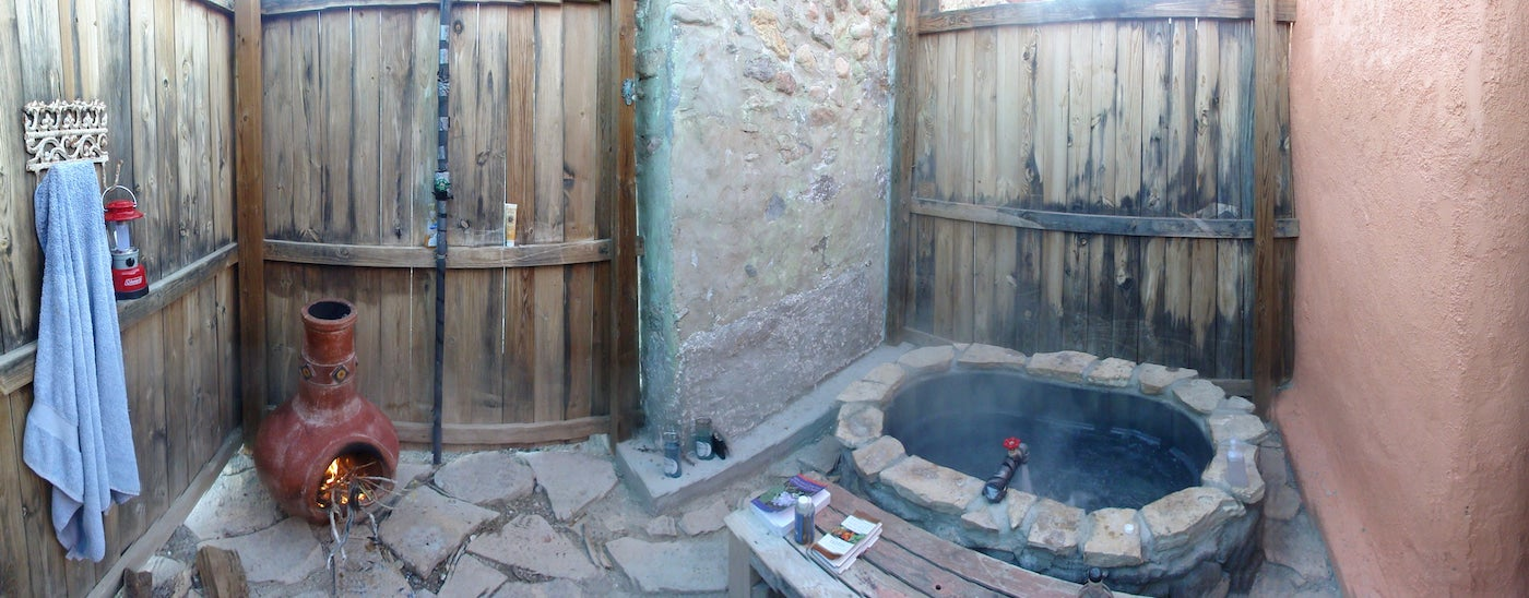 Closed in room with wooden doors and hot spring stone tub.