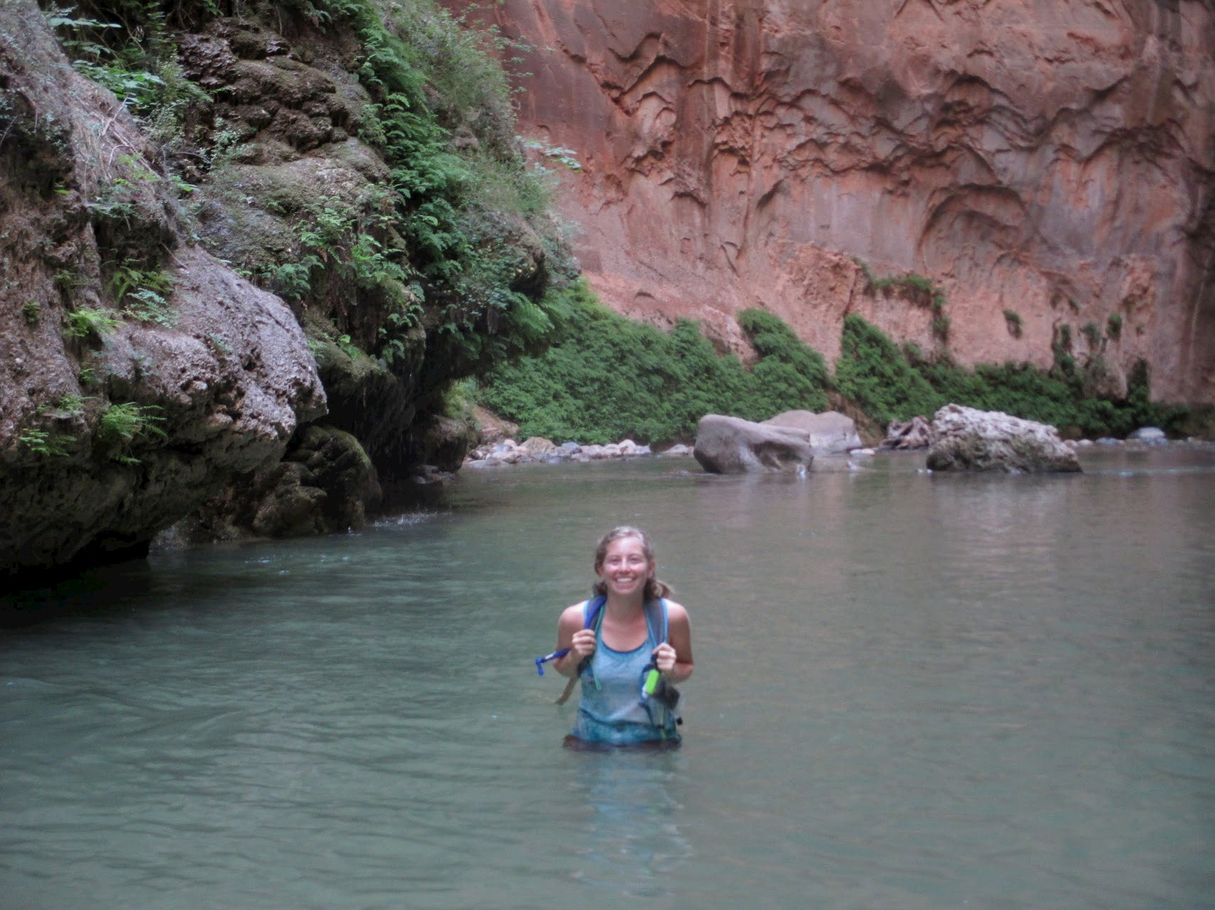 Women with backpack wading through water in a canyon.
