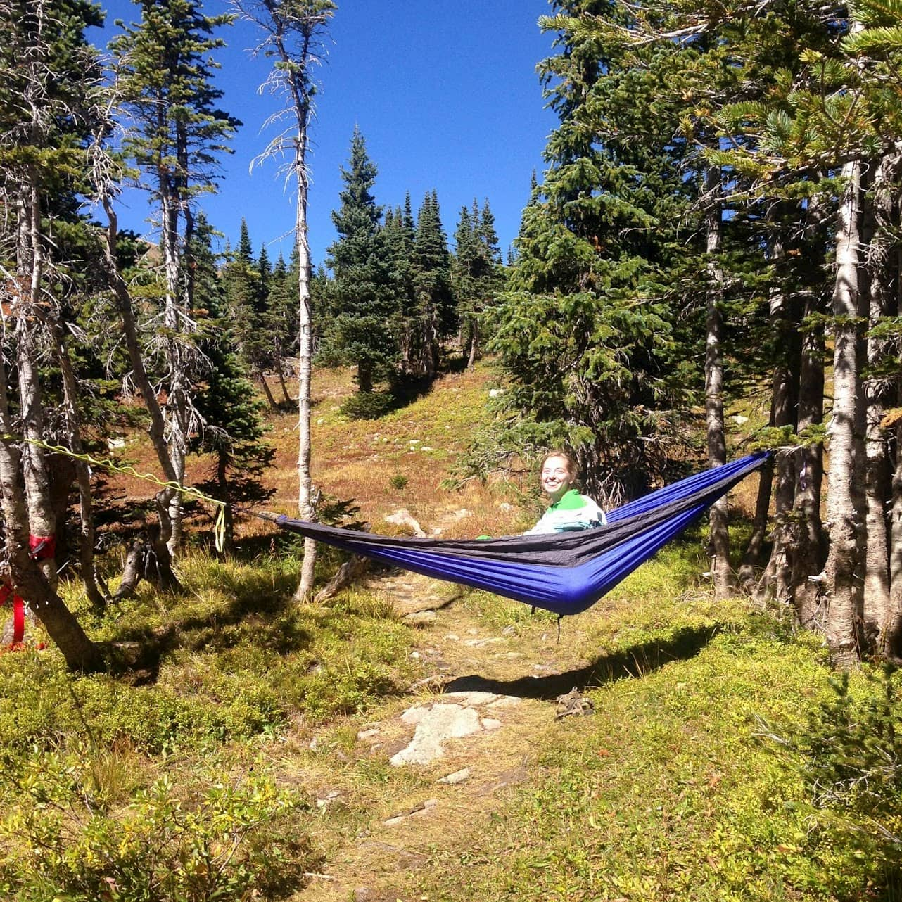 Women peeping out of hammock between two trees in the backcountry.